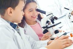 Petits enfants apprenant la chimie dans le laboratoire d'école image libre de droits