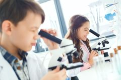 Petits enfants apprenant la chimie dans le laboratoire d'école regardant dans des microscopes photos stock