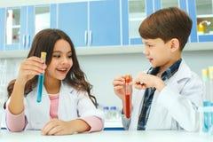 Petits enfants apprenant la chimie dans le laboratoire d'école tenant des fioles photos libres de droits