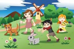 Petits enfants avec des animaux familiers dans le jardin Photos stock