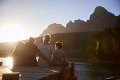 Petits-enfants avec des grands-parents s'asseyant sur la jetée en bois par le lac images libres de droits