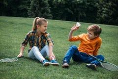 Petits enfants avec des raquettes de badminton et volant se reposant sur l'herbe au parc Photo stock