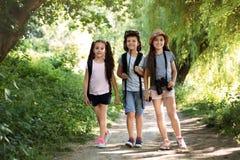 Petits enfants avec des sacs à dos sur le chemin dans la région sauvage Image stock