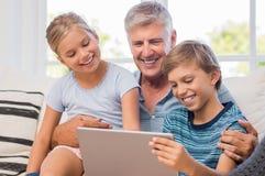 Petits-enfants avec le grand-père à l'aide du comprimé photos stock