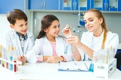 Petits enfants avec le professeur dans le laboratoire d'école expliquant la réaction photo stock