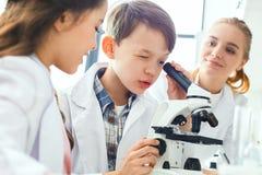 Petits enfants avec le professeur dans le laboratoire d'école regardant en plan rapproché de microscope image libre de droits