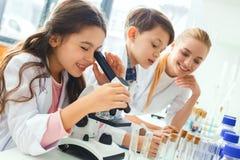 Petits enfants avec le professeur dans le laboratoire d'école regardant dans le microscope photos libres de droits