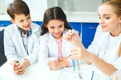 Petits enfants avec le professeur dans les liquides de mélange de laboratoire d'école Photo libre de droits