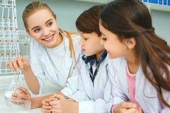 Petits enfants avec le professeur en ingrédients de mélange de laboratoire d'école Image libre de droits