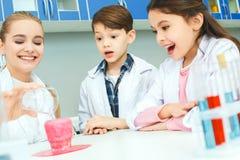 Petits enfants avec le professeur en plan rapproché acide de réaction de laboratoire d'école Photo libre de droits