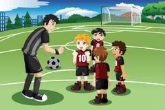 Petits enfants dans le terrain de football écoutant leur entraîneur Image libre de droits