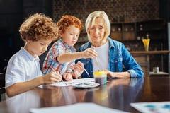 Petits-enfants de enseignement de grand-maman affectueuse peignant à la maison images stock