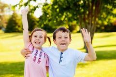 Petits enfants de mêmes parents heureux embrassant et ondulant des mains Photographie stock libre de droits