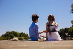 Petits enfants de mêmes parents mignons s'asseyant sur le pilier et ayant des casse-croûte Photo libre de droits