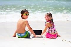 Petits enfants de sourire avec l'ordinateur portable sur la plage Photographie stock libre de droits