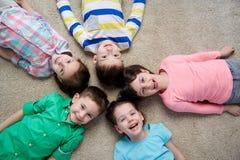 Petits enfants de sourire heureux se trouvant sur le plancher Images libres de droits