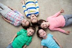 Petits enfants de sourire heureux se trouvant sur le plancher Photo libre de droits