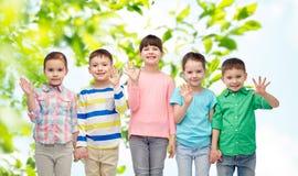 Petits enfants de sourire heureux tenant des mains Photos stock