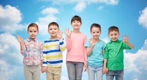 Petits enfants de sourire heureux tenant des mains Images stock