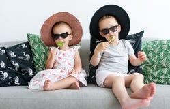 Petits enfants en verres noirs se reposant avec des lucettes sur l'entraîneur dans le salon à la maison avec des chapeaux Images stock