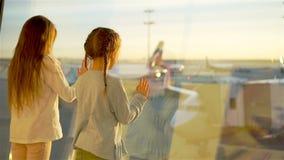 Petits enfants ensemble dans l'embarquement de attente d'aéroport près de la grande fenêtre banque de vidéos
