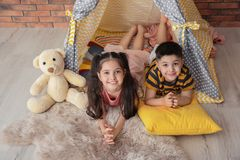 Petits enfants espiègles dans la tente faite main photographie stock
