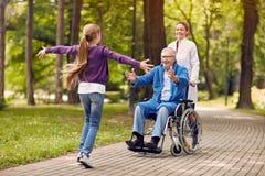 Petits-enfants gais rendant visite au père handicapé en parc Photographie stock libre de droits