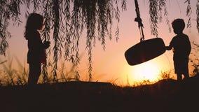 Petits enfants, garçon et fille jouant avec l'oscillation près du lac pendant le beau coucher du soleil banque de vidéos