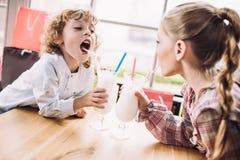 Petits enfants heureux buvant des milkshakes avec des pailles en café Images libres de droits