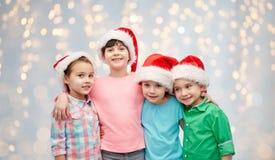 Petits enfants heureux dans étreindre de chapeaux de Santa Photographie stock