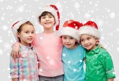Petits enfants heureux dans étreindre de chapeaux de Santa Images libres de droits