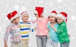 Petits enfants heureux dans étreindre de chapeaux de Santa Image stock