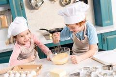 petits enfants heureux dans des chapeaux de chef et tabliers battant la pâte photo libre de droits