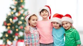 Petits enfants heureux dans des chapeaux de Santa de Noël Photographie stock libre de droits