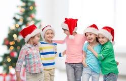 Petits enfants heureux dans des chapeaux de Santa de Noël Photos stock