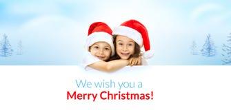 Petits enfants heureux dans le chapeau de Santa jetant un coup d'oeil par derrière Image stock