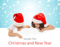 Petits enfants heureux dans le chapeau de Santa jetant un coup d'oeil par derrière Photos libres de droits