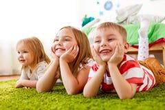 Petits enfants heureux se trouvant sur le plancher ou le tapis Photographie stock libre de droits
