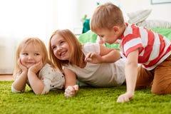 Petits enfants heureux se trouvant sur le plancher ou le tapis Photo libre de droits