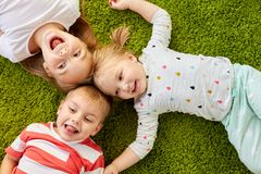 Petits enfants heureux se trouvant sur le plancher ou le tapis Images libres de droits