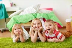 Petits enfants heureux se trouvant sur le plancher ou le tapis Photos stock