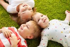Petits enfants heureux se trouvant sur le plancher ou le tapis Photographie stock
