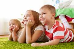 Petits enfants heureux se trouvant sur le plancher ou le tapis Image libre de droits