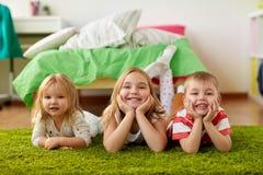 Petits enfants heureux se trouvant sur le plancher ou le tapis Images stock