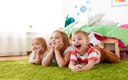 Petits enfants heureux se trouvant sur le plancher ou le tapis Photo stock