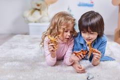 Petits enfants intéressés jouant avec des chiffres animaux de safari Images stock