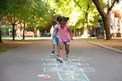Petits enfants jouant le jeu de marelle dessiné photographie stock