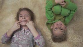 Petits enfants joyeux dans des pyjamas se trouvant sur le plancher avec le tapis pelucheux Le frère et la soeur ont un amusement  banque de vidéos