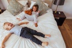 Petits enfants joyeux jouant sur le lit Image libre de droits