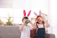 Petits enfants mignons dans des bandeaux d'oreilles de lapin tenant des oeufs de pâques près des yeux à la maison photographie stock libre de droits